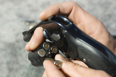 Close up of man's hand reloading pistol chamber